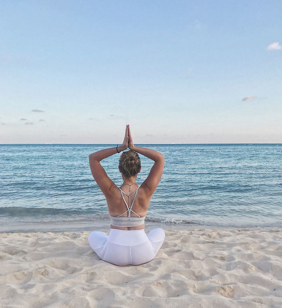yogaplusexercise.weebly.com yoga plus exercise on the beach.  Solo.  Pose is Sun salute sitting cross-legged